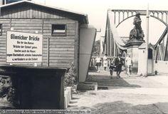 """2200 Brücke der Einheit: Glienicker Brücke (seit 1949 auf Beschluss des Landes Brandenburg trägt die Potsdamer Brückenhälfte den Titel: """"Brücke der Einheit"""") um 1970 mit einem offiziellen Straßenschild der Stadt Berlin (West) zur Erklärung der Situation."""