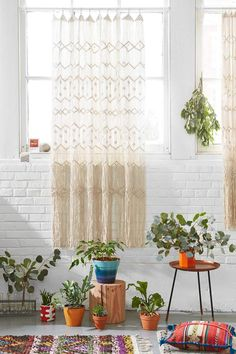 Macrame wall hanging against a white brick wall - Decoist