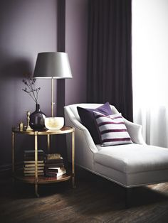 Extending the pure purple from the wall to the drapes creates a sumptuous cocooning effect. Incorporate a grey linen chaise by layering it with solid and striped plum velvet pillows and paint a paper shade in a complementary soft grey.