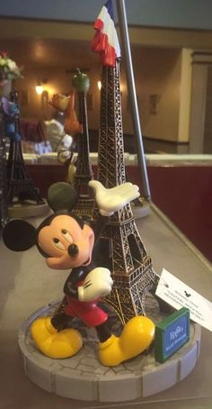 "Mickey+is+touring+the+city+of+love!+Commemorate+your+trip+to+Paris+at+Epcot's+World+Showcase+with+this+Mickey+in+front+of+la+tour+Eiffel+figurine+with+flag+on+the+top!+Fully+sculptured+figures+Resin+7+1/2""+H+x+4+1/4""+D+new+with+tags"