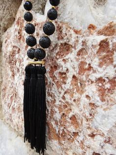 Black Gem necklace  Handmade long beaded silk cord necklace embellished with black gemstones, black onyx, lava stones, glass beads, crystal stones, gold plated elements and black tassels. Wear yours to add a statement finish to a simple tee or dress.  The size is adjustable because of the macrame closure.   Our Items are handmade and may have slight variations between the same items. Minor imperfections can be possible on leathers, which is what makes them unique!  Colors may vary slightly…