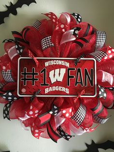 "Wisconsin Badger Mesh Wreath. This wreath is made on a red mesh. It features a Wisconsin Badgers #1 Fan centerpiece surrounded by lots of red, white and black high quality wired ribbons. This wreath measures approximately 23"" in diameter. What a great way to show your support for your favorite team and to welcome your family and friends to your home."
