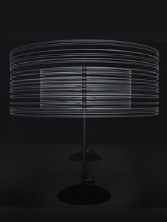 carsten nicolai, moiré rota is constituted by two rotating columns with attached cable strings that at the end hold a LED. by rotation the LED lights create light rings around the columns that by visual superimposition result in ever-changing light moirés.