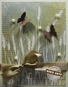 "By Shari Carroll. Uses ""Silhouette Grass"" stamp by Hero Arts. Stamp grass in VersaMark on white cardstock & emboss in clear powder. Sponge on Distress ink: old paper, weathered wood, scattered straw. Stamp text with pumice stone Distress ink. Buff. Add ribbon & attach to card base."