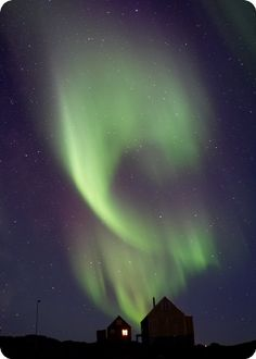 Aurora Borealis spirals over a house in Greenland
