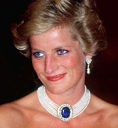 Princess Diana wearing the Emir of Qatar earrings with a pearl choker, set with the sapphire brooch given to her by Queen Elizabeth, Queen Mother. The Queen Mum had more gifts in store for Diana; for her wedding, she gave her new granddaughter-in-law a large oval sapphire and diamond brooch. In the early years of her marriage, Diana wore the piece as a brooch, but she quickly had it converted into the clasp of a seven-strand pearl choker. This was one of the large pieces of jewelry that…