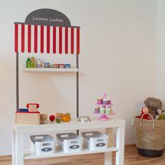 http://www.wandmotive.de/Kaufen/Aufkleber-fuer-IKEA-Moebel/ Aus einer kleinen TV-Bank und einer Bilderleiste von Ikea entsteht ruckzuck ein schicker Kaufladen. Man braucht dazu nur das Stickerset von Wandmotive.de, das sich ganz leicht anbringen lässt. Der Kaufladen ist sogar personalisierbar!