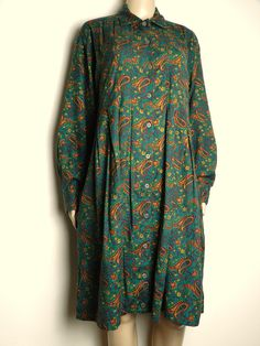 Vintage 80s 90s loose fitted mid length shirt tent / shirt dress.  Fabric is a medium weight blend of wool and cotton.  Rich emerald green with rust red and golden yellow paisley print.  Front and cuffs close with coconut shell buttons.  Two hidden waist pockets in the skirt folds.