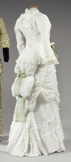 """Robe d'été à tournure """" à la Polonaise""""en linon, vers 1880- 1885. Robe en deux parties au corsage boutonné à manches longues souligné d'un fin ruché et d'une jupe à tablier relevé bouilloné dans le dos, ornée d'un large noeud de taffetas rayé vert et blanc (bel état)."""