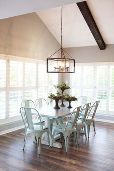 Find this stylish farmhouse dining room on www.recreatearoom.com. Click visit to find out where to get the unique chandelier, distressed white table, and rustic metal chairs.