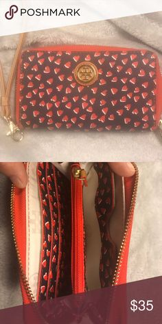 "Tory Burch Wristlet Tory Burch Kerrington Smartphone Wristlet in Valentines Amore - New with tags  Smartphone wristlet in a coated vinyl in a red heart pattern.  It zips around three sides in a gold zipper with a gold zip pull and has a detachable wristlet strap.  The inside of the wallet is leather and has 3 slots for credit cards, a center zip compartment with a Tory Burch logo zipper pull and a pocket for your cell phone.  Dimensions are approximately 6"" by 4"".  Stored in a non-smoking…"