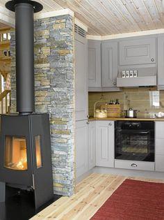 LUN PEIS: Peisovnen gir godt med varme og er et stemningsskapende innslag på kjøkkenet. Den røde ryen er en fargeklatt i rommet.