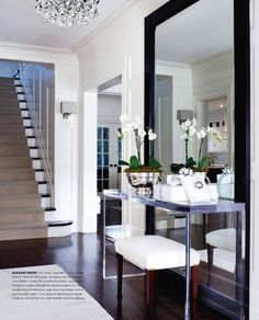 Entry says elegance and sophistication. Glass-topped chrome table, simple black framed mirror, simple bench and orchid in silver bowl. Chandelier seems to be appropriate size.