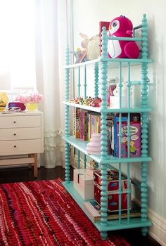 Sweet girl's room with Land of Nod Jenny Lind Bookcase in Azure filled with books, stuffed animals and Japanese eraser collection.