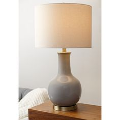 This gourd-shaped table lamp features a brushed ceramic base in a handsome gray with a high-gloss finish and a classic ivory shade. This stylish Abbyson lamp looks great in your home or office.