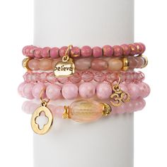 "Rose quartz, pink riverstone, lepidolite, and glass set of five with gold tone di-cut clover, ""Believe"", and Ohm charms, measures approximately 7.5"" in length. With the purchase of this bracelet set, 25% of gross proceeds goes to the Dr. Susan Love Research Foundation.  $50.00  @Julie Marie Chavez"