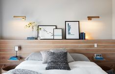 Since we were working with limited space, I knew that fitting two classic side tables and a headboard would be a stretch, so instead we installed the same white oak wall treatment from the entryway to serve as a headboard, a ledge for layering art and family photos, and modified side tables.