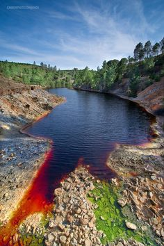 As a result of the mining, Río Tinto is notable for being very acidic (pH 2) and its deep reddish hue is due to iron dissolved in the water. Acid mine drainage from the mines leads to severe environmental problems due to the heavy metal concentrations in the river