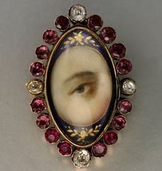 Lover's eye gold brooch, 19th century. Miniature painting of an eye with yellow gold, diamonds, garnets, glass, blue enamel. Provenance - Promenade Galleries, Peacehaven, East Sussex, England. Another photo below.