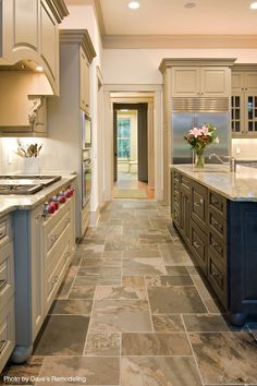 Eclectic kitchen with multi-colored cabinets, a huge island, undercabinet lighting, tile floors, ceramic tile floors and granite counters. That custom range looks perfect for any home chef. Click on the pin to see our money-saving tips for all kitchen remodels.
