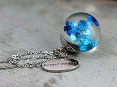 Floating bright forget me nots in resin orb. Silver colored necklace with forget me not charm . resin, dried forget me nots, brass . made to order . necklace length: 27'' . $23.90