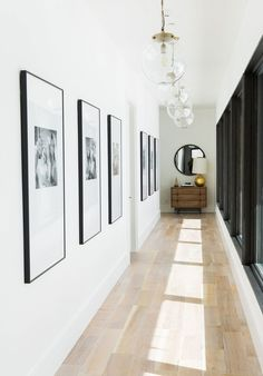 Pendant lights by Arteriors hang in the light-filled hallway | http://archdigest.com ~ Great pin! For Oahu architectural design visit http://ownerbuiltdesign.com