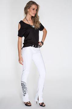 A blusa preta com recorte nos ombros e aplicação de tachinhas forma a dupla clássica com a calça branca com tigre bordado na lateral e abertura na barra.