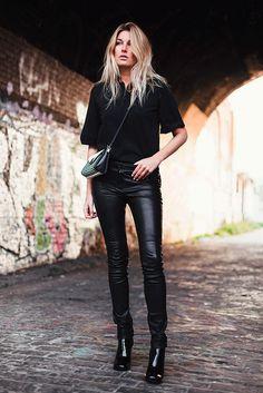 Street style look total black com calça resinada, bota verniz e bolsa transpassada.
