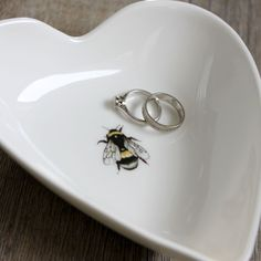 This elegant fine bone china occasion bowl features a stunning bumblebee print and is beautifully presented in a black gift box with ribbon. Whether it's to serve up delicious dips and nibbles or as a stunning keepsake to place wedding rings, cufflinks and jewellery, this china dish makes the perfect present for years to come. Pair with matching Bumblebee Milk Jug. The superb print quality of these dishes captures the fine detail and vibrant colours of the watercolour design ba...