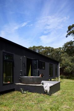 Completed in 2018 in Fish Creek, Australia. Images by Armelle Habib, Tom Ross. Among towering trees of Fish Creek sits a small, off-the-grid holiday home that eschews clichés of traditional beachside escapes - a sustainable. Rustic Color Schemes, Rustic Colors, Outdoor Baths, Outdoor Bathrooms, Dulux Natural White, Off Grid House, Off The Grid Homes, Stone Bath, Fish Creek