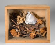 """Meret Oppenheim  1913 Berlin – 1985 Basel  """"Le Cocon (il vit)"""". 1974 Wooden box with sheet of acrylic glass, filled with foliage, dried branches, roses and a cushion. 13 x 16 x 9,5 cm (5 ⅛ x 6 ¼ x 3 ¾ in.) Monogrammed and dated on the cushion. Curiger X 232. One of 99 numbered copies."""