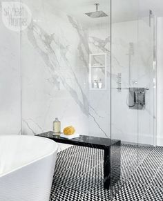 The shower's Nero Marquina marble bench is a functional element that offers a hit of contrasting black and serves as a striking decorative piece. | Image: Stephani Buchman