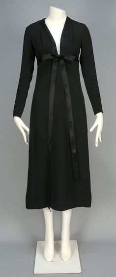 YVES SAINT LAURENT COUTURE COCKTAIL DRESS, 1969. Black silk crepe having long zippered sleeve, plunging V-neck edged in satin, high waist with satin sash and narrow A-line skirt