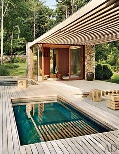 Small swimming pool captured within wood deck.