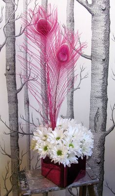 Simple white chrysanthemum centerpiece with dyed, hot pink, peacock feathers.