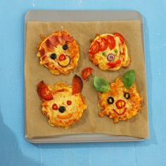 Four mini pizzas with toppings that look like faces on a wooden board.