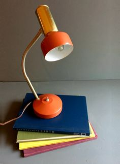 Theres nothing handier than being able to redirect light to shine right down on where you need it. This lil gal is sleek and stylish, and comes in a color I havent run across many times - a bright coral/deep orange tone that stands out with gold and chrome details and smooth lines.  This lamp is great for an office desk or perhaps an art studio or craft room - the long, flexible neck on it allows for specific, redirected light on your most important projects or assignments. Its in excel...