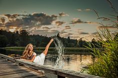 Senior pose of ballet girl in lake kicking up water.