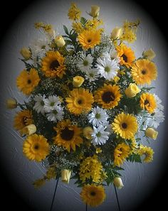 Yellow Sunflowers, yellow Gerbera Daisies, yellow Roses and Daisies beautifully arranged in a funeral side spray for your loved one.