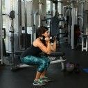 Stand with feet hip-width apart holding 15-pound dumbbells just above shoulders, palms facing in. Engage core, hinge at hips, and bend knees to a squat.