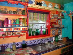 Amazingly colorful bohemian kitchen. Love the idea of tiling the entire sink countertop area with brightly colored tiles. It gives such personality.