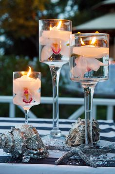 White orchids in floating candle holders compliment the beachy feel of the surrounding seashells.