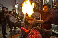 Ramadan Edwan, a Palestinian barber, uses fire in a hair-straightening ...