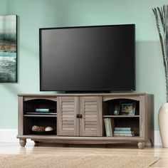 """Holds up to a 60"""" TV • Hidden storage behind louver-detailed doors • Three adjustable shelves"""