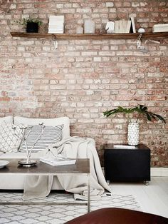 Minimalist living space with exposed brick walls | @andwhatelse
