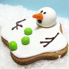 "Take a bite out Frosty before he melts away!                 What you'll need: dough, frosting, soft gel pastes (white, orange, green), sharp knife, frosting bag, small spatula or knife, white rolled fondant, black edible pen, light corn syrup                 Make it: Bake a ""blob"" shaped cookie and let cool. To decorate, color frosting with white gel paste and spread across the cookie. Once your base is set, roll some fondant between your palms to form a sphere for the head (colored white) ..."