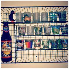 Kitchen drawer organizer hung on wall as shot glass display.