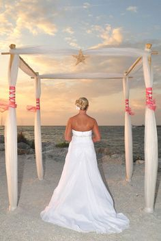 A stunning bride in a four post bamboo arch with pink sashes 'laced' around the posts and a central starfish. Suncoast Weddings present another sensational Florida beach wedding style.