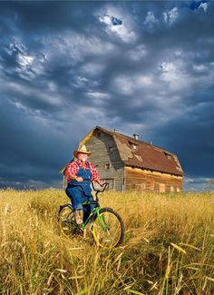 Man On John Deere Bike By A Barn In Old Farm Field