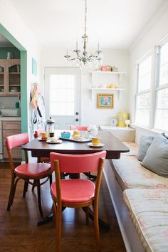 Dark wood dining table + pale mustard yellow ceramics + pink/off-red chairs + white walls!!!